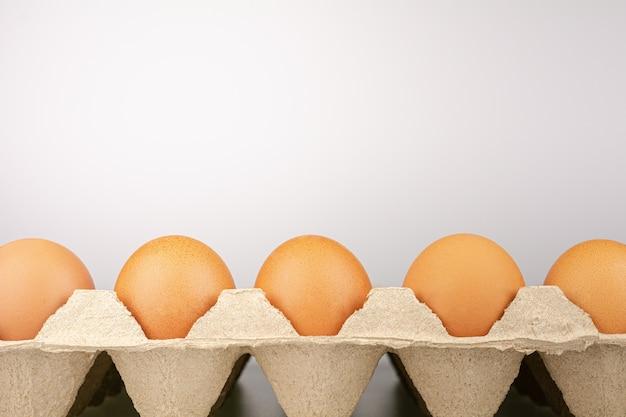 Vista sopraelevata delle uova fresche del pollo marrone in un cartone aperto dell'uovo.