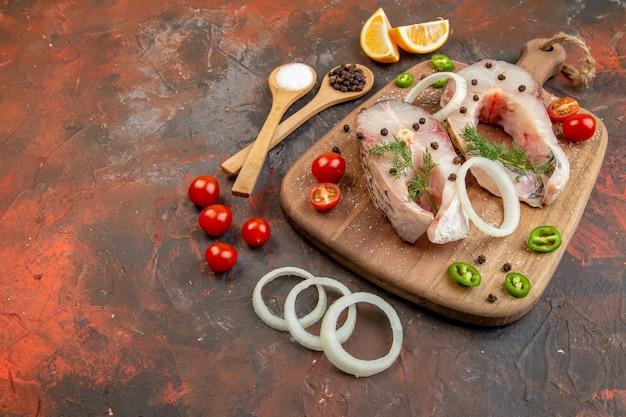 Vista dall'alto di pesce crudo fresco e pomodori verdi cipolla pepe su tagliere su superficie di colore misto mixed