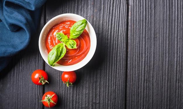 Una vista aerea di salsa di pomodoro fresco con panno sulla tavola di legno