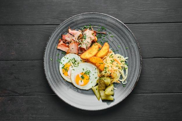 Vista dall'alto di uova fritte, prosciutto con spicchi di patate, cavolo in salamoia e cetriolo sul tavolo di legno nero black