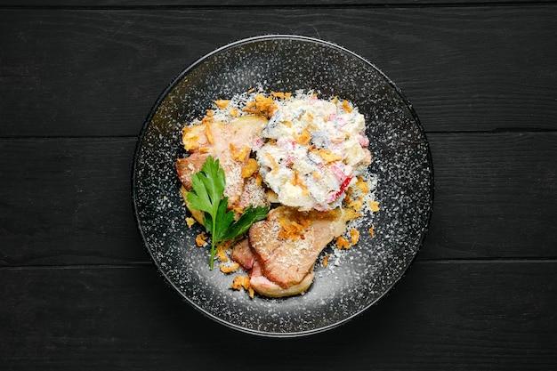 Vista dall'alto del prosciutto fritto con insalata cosparsa di scaglie di pancetta e parmigiano grattugiato su un piatto