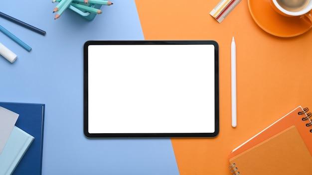 Vista dall'alto di mock up tablet digitale con schermo vuoto circondato da tazza di caffè, notebook e articoli di cancelleria su due toni di sfondo blu e arancione.