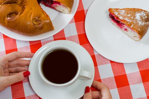 Foto vista dall'alto di torta di ciliegie fatta in casa e tazza di tè sulla tovaglia a scacchi
