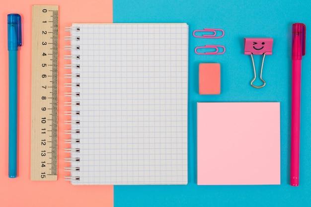 Foto vista dall'alto di materiale scolastico. set di quaderni a spirale, gomma, righello, penne, adesivi, clip su sfondo mezzo blu e mezzo rosa