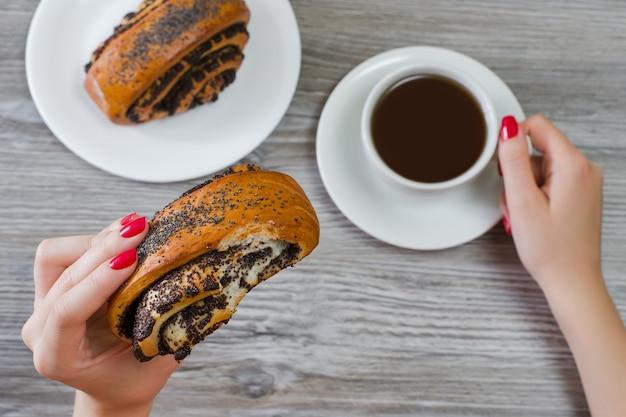 Foto vista dall'alto delle mani di una donna che tengono un panino morso con semi di papavero e una tazza di caffè