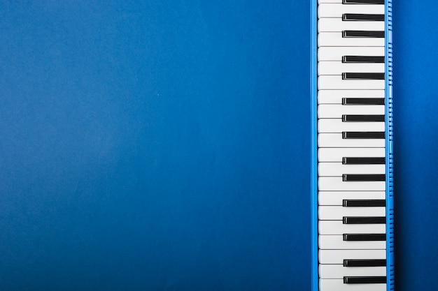 Una vista aerea della tastiera del pianoforte su sfondo blu