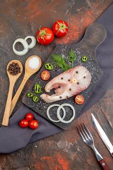 Vista dall'alto di pesce crudo e peperoni verdi cipolla pomodori su tagliere nero su posate asciugamano su superficie di colore misto