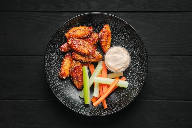 Vista dall'alto di ali di pollo arrosto, bastoncini di sedano e carota e salsa su un piatto