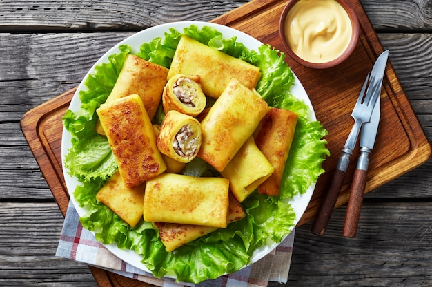 Vista dall'alto di involtini di crepe salati con carne di pollo macinata e ripieno di champignon serviti su un piatto di foglie di lattuga fresca su un piatto bianco su un tagliere con salsa chesse, flatlay, close-up