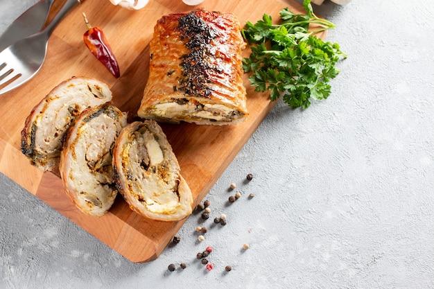 Vista dall'alto dell'involtino di maiale arrosto a fette - porchetta, delizioso arrosto di maiale della tradizione culinaria italiana su un tavolo di pietra stone