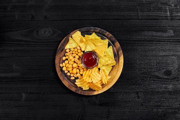 Vista dall'alto di snack con salsa sul tavolo di legno nero