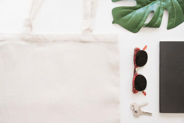 Vista dall'alto di occhiali da sole, chiave, tote bag e foglia di monstera su sfondo bianco