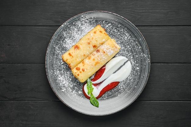 Vista dall'alto di crepe sottili con ricotta e marmellata di fragole su un piatto