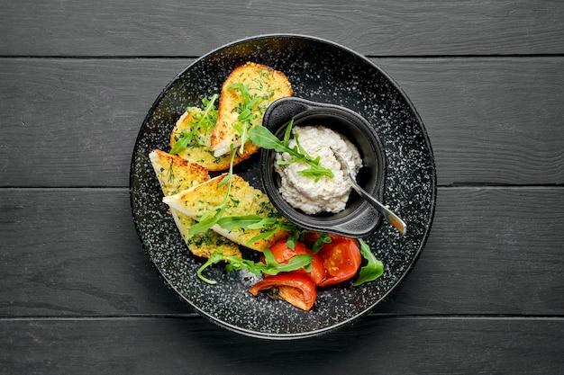 Vista dall'alto di pane all'aglio tostato, pomodoro e paté di pollo su un piatto