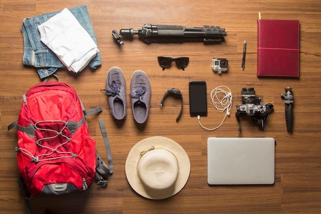 Vista sopraelevata del fondo di concetto degli accessori del viaggiatore