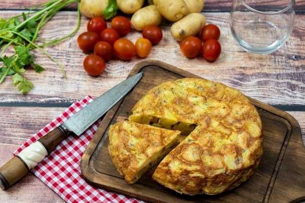 Vista dall'alto di una tipica frittata di patate o patate spagnola con una porzione separata con patate e pomodorini in un ambiente rustico. cucina tradizionale spagnola. Foto Premium