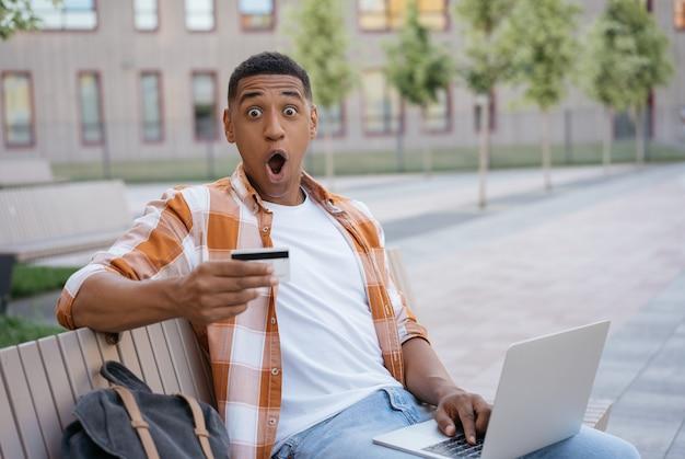 Uomo afroamericano felicissimo con carta di credito che fa acquisti online con grandi vendite il black friday