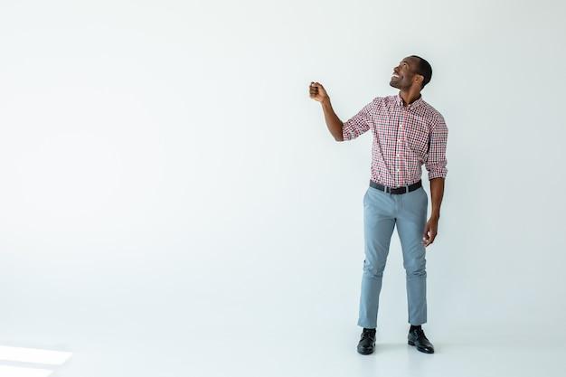 Uomo afroamericano felicissimo che si gode il tempo mentre si tiene un ombrello