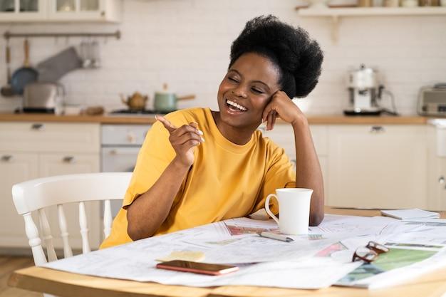 La donna d'affari nera felicissima ride il lavoro da casa architetto allegro si siede al tavolo con i progetti