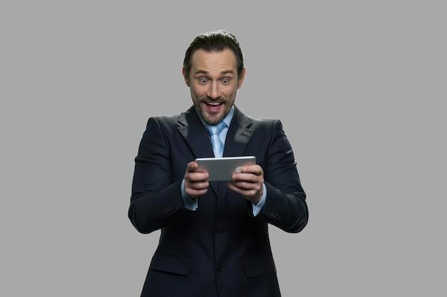 Uomo d'affari felicissimo utilizzando smartphone. imprenditore godendo di giocare online su sfondo grigio. uomini d'affari, tecnologia e divertimento.