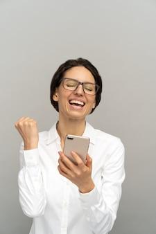 Imprenditrice felicissima leggendo il messaggio sullo smartphone, mostrando il gesto di sì, godendo di buone notizie