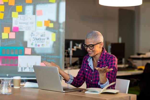 Donna di affari creativa felicissima che si siede sulla scrivania in ufficio