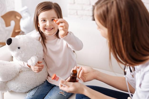 Bambina felicissima che mostra la pillola e la prende mentre è seduta sul divano con un medico professionista