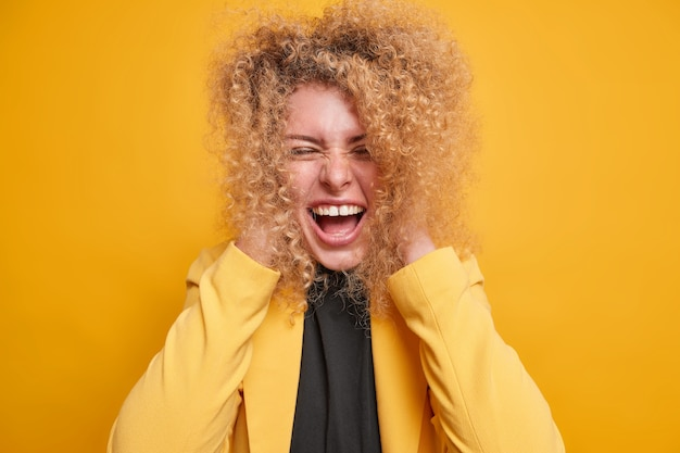 La donna dai capelli ricci divertente e contenta tiene le mani sulla testa ride divertito da qualcuno ha un'espressione ottimista vestita con abiti eleganti isolati sul muro giallo. concetto di emozioni felici