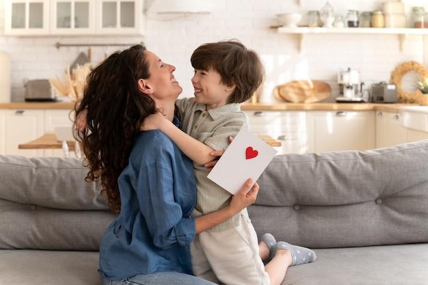 La mamma felicissima celebra la festa della mamma abbraccia il simpatico figlio di cinque anni e tiene la carta con i saluti di un bambino piccolo