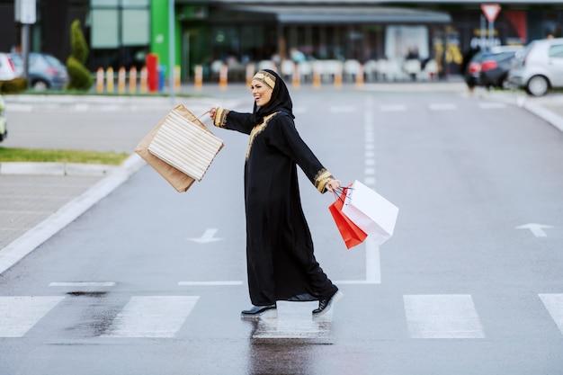 Felicissima donna musulmana sorridente positiva in abiti tradizionali che porta le borse della spesa in mano e si sente soddisfatta dei suoi acquisti mentre attraversa la strada.