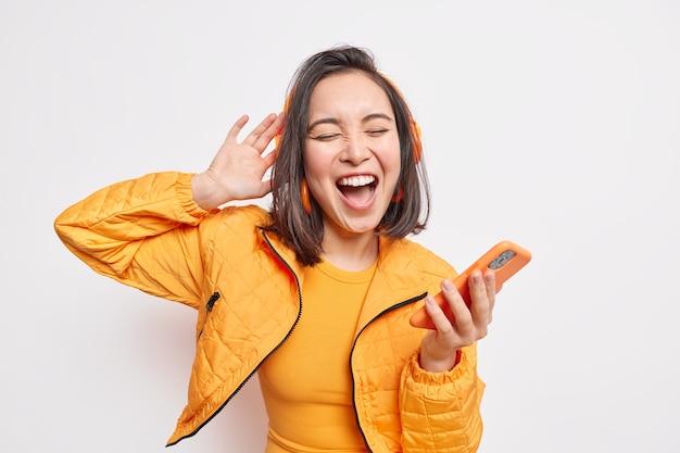 La bella ragazza asiatica felicissima si è lasciata trasportare dalla musica tiene lo smartphone si gode la playlist preferita tramite le cuffie stereo ha un'espressione spensierata rilassata canta insieme indossa una giacca arancione