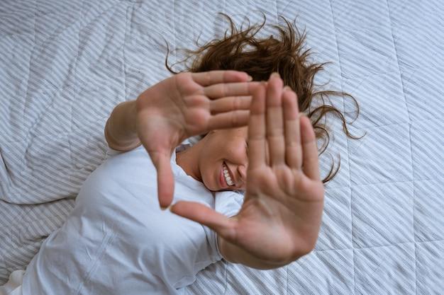 Donna felicissima in pigiama che allunga le braccia dopo essersi svegliata sdraiata in un letto accogliente sorride...