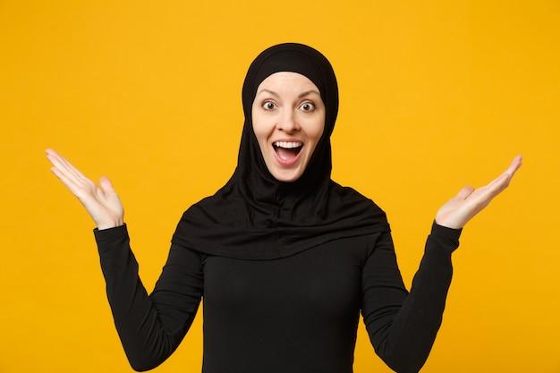 Felice giovane donna musulmana araba in abiti neri hijab che fa il gesto del vincitore, dì sì isolato sul muro giallo, ritratto concetto di stile di vita religioso della gente.