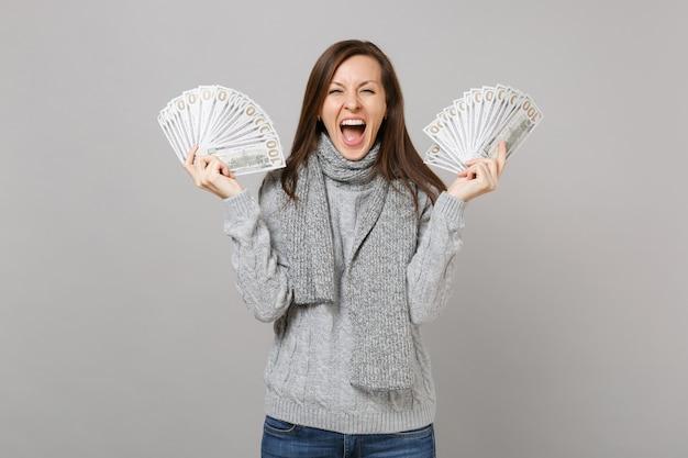 Felice giovane donna in maglione grigio sciarpa urlando, tenendo un sacco di banconote in dollari, denaro contante isolato su sfondo grigio. stile di vita sano, emozioni delle persone, concetto di stagione fredda.