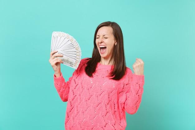 Giovane donna felicissima in maglione rosa che urla, tiene in mano un sacco di banconote in dollari, denaro contante, pugno serrato come vincitore isolato su sfondo blu. concetto di stile di vita della gente. mock up copia spazio.