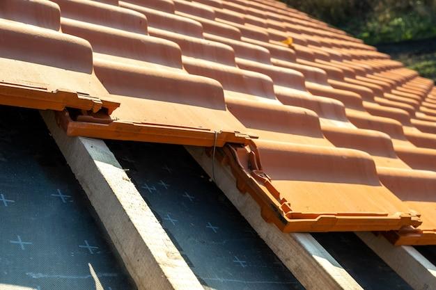 Righe sovrapposte di tegole in ceramica gialla montate su assi di legno che coprono il tetto di un edificio residenziale in costruzione.