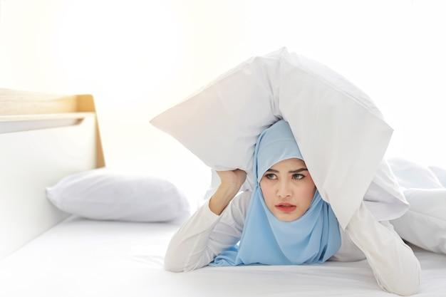 Dormire troppo donna musulmana asiatica in indumenti da notte sdraiato sul letto e manca l'anello della sveglia svegliarsi.