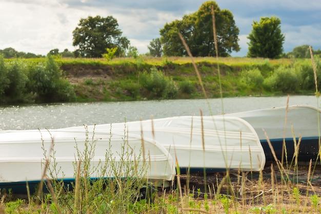 Kayak rovesciato sulla riva del fiume. paesaggio estivo