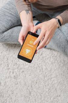 Panoramica delle mani femminili attive che tengono lo smartphone sul pavimento mentre si preme il pulsante di pausa per guardare il video di yoga
