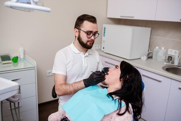 Panoramica sulla prevenzione della carie dentale. donna alla poltrona del dentista durante una procedura dentale
