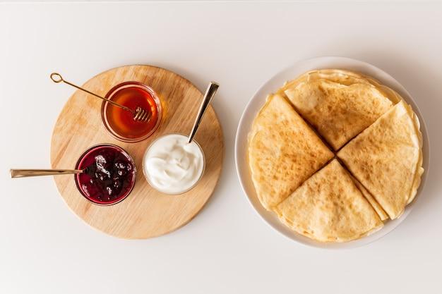 Panoramica di frittelle piegate fresche fatte in casa sul piatto e piccole ciotole di vetro con miele, marmellata di ciliegie e crema acida su tavola di legno
