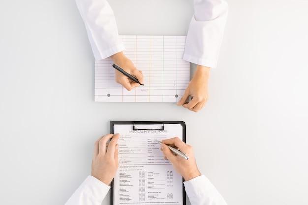 Panoramica delle mani del medico che compila il modulo di storia medica negli appunti e del suo assistente o infermiere con la penna che prende appunti sulla scheda in bianco