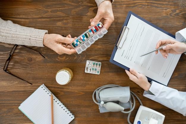 Panoramica delle mani di un uomo anziano malato che tiene in mano un contenitore con pillole sul tavolo durante la consultazione medica con il medico che compila il documento
