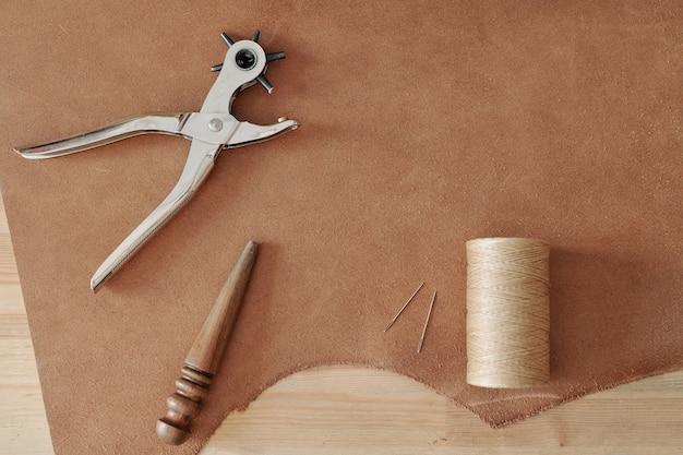 Panoramica dell'utensile manuale per fare buchi, rocchetto con fili leggeri, due aghi e utensile in legno su parte di camoscio beige