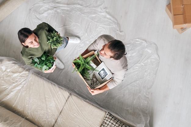 Panoramica di felice giovane uomo e donna con verdi piante domestiche in piedi sul pavimento da divano in soggiorno
