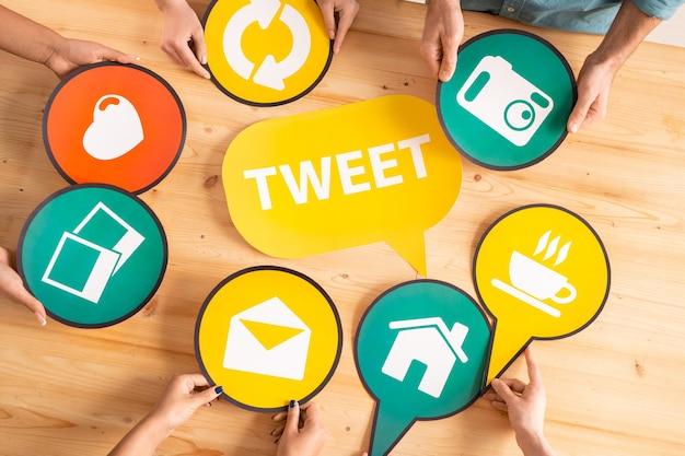 Panoramica delle mani dei millennial che tengono i fumetti di carta scelti con le icone dei social network intorno a quello giallo sulla tavola di legno Foto Premium