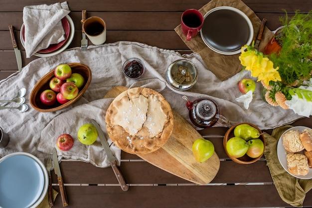 Panoramica del tavolo rettangolare in legno servito con torta e focacce fatte in casa, frutta fresca e fiori dell'orto e tè con marmellata e zucchero