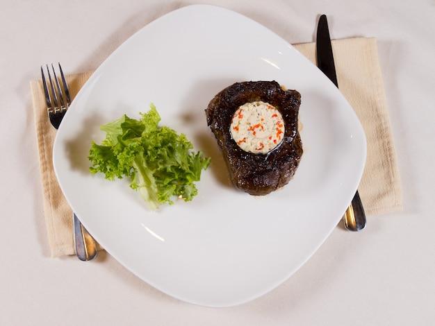 Panoramica della bistecca condita con burro alle erbe sul piatto al posto sul tavolo