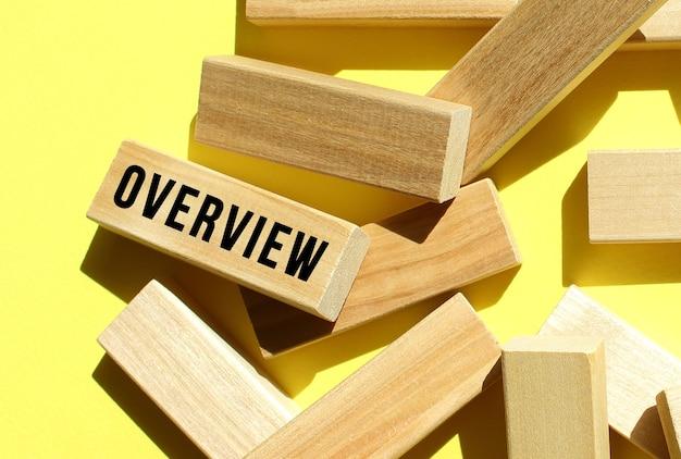Il testo overview è scritto su uno dei tanti blocchi di legno sparsi, su sfondo giallo. concetto di affari.
