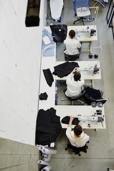 Panoramica di tre giovani donne sedute da macchine da cucire elettriche in officina durante il loro lavoro sulla collezione di moda stagionale